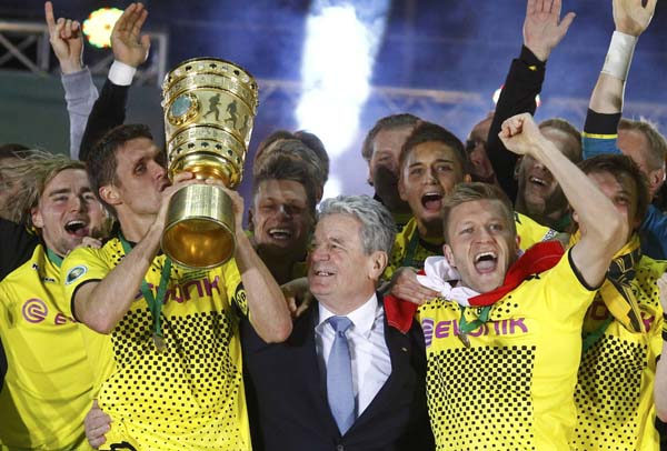 Borussia Dortmund's Sebastian Kehl (L) kisses the trophy as the team celebrates after defeating Bayern Munich to win the German DFB Cup final soccer match in Berlin